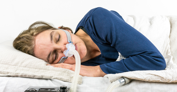 a woman sleeping with a CPAP mask