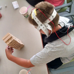 Boy fitted with brain stimulation headgear used in the study manipulates blocks.