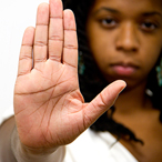 Young adult with stop gesture hand sign