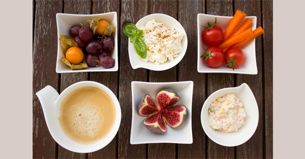 Six small differently shaped dishes with fruit salad, bite-sized vegetables, and other foods