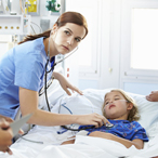 Hospital staff attend to a child in bed in the pediatric critical care ward, while the child's mother stands by the bed