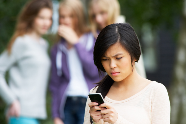 Teen girl with concerned look on her face looking at a mobile device, while in the background, a blurred group of teen girls is whispering and looking at the girl with the mobile device