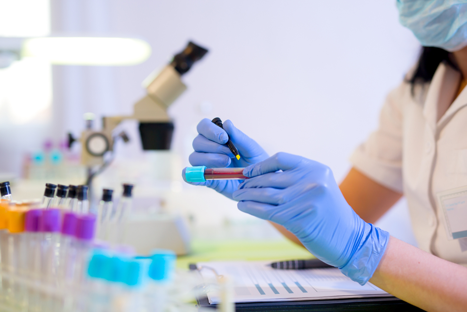 Researcher marking a test tube containing a blood sample in a medical laboratory, with a microscope in the background and other test tubes in the foreground.