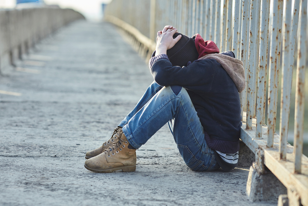 Young person alone, sitting next to a fence along a sidewalk, head down, hiding his or her face