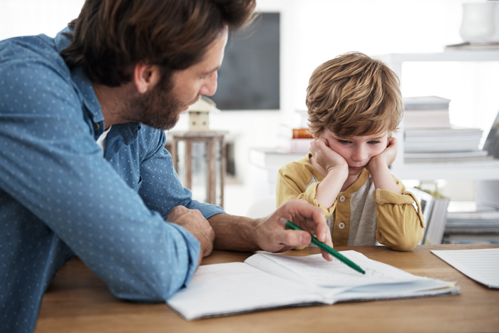 Stock image of an adult male points to a notebook page and a child looks on, discouraged, with head in hands.