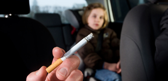 A hand holding a lit cigarette is visible inside a car with a young girl sitting in the backseat.