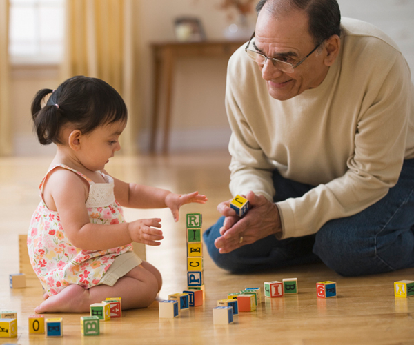 Image of a grandfather smiling at a toddler playing with alphabet blocks.