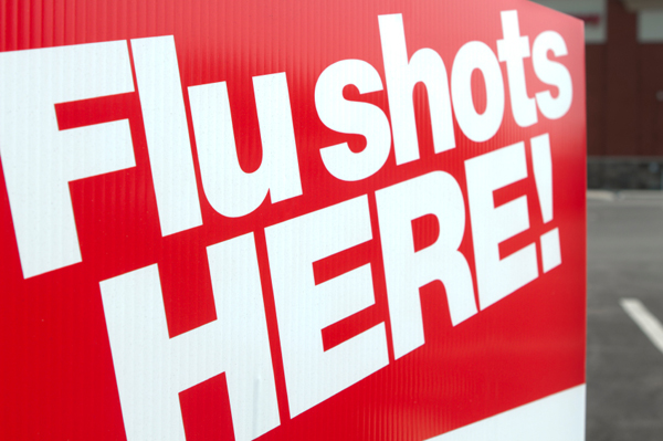 A sign advertises flu vaccines, with the words 'Flu Shots HERE!'