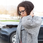 Woman standing in front of a two car crash, massaging the back of her neck, grimacing in pain.