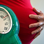 pregnant woman's abdomen, her arm holding a bathroom-style scale
