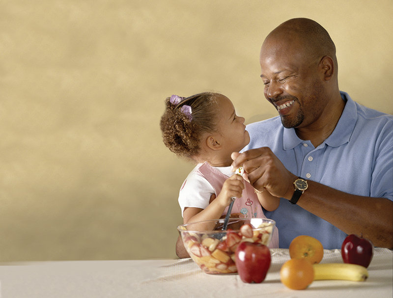 Stock image of man with little girl sharing healthy food.