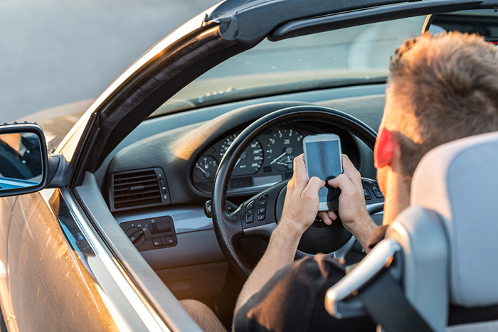 Stock image of a teenage boy using cell phone with two hands behind the wheel.