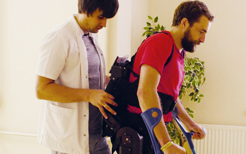 A male nurse helping a young man with a disability walk in a robotic skeleton.