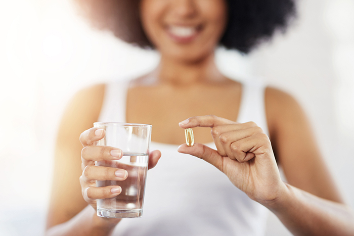 Stock image of a woman holding a glass of water and a pill sized capsule.