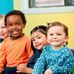 Five toddlers are standing or sitting in a row, smiling. The group is ethnically diverse and a mix of boys and girls.