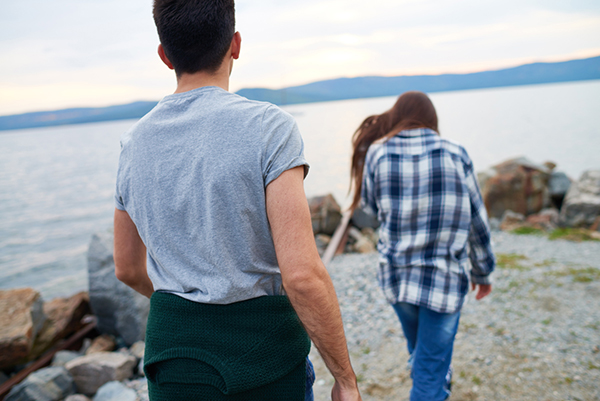 Stock image of a young couple on the shore of a river or a lake, the woman appears to be walking away from the man.