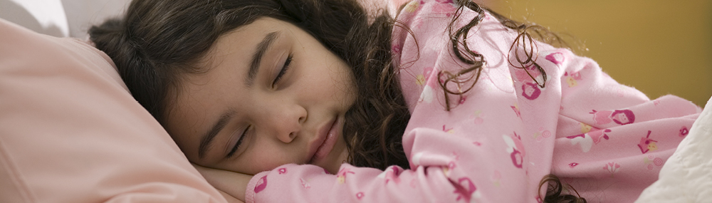 A young girl asleep in bed.