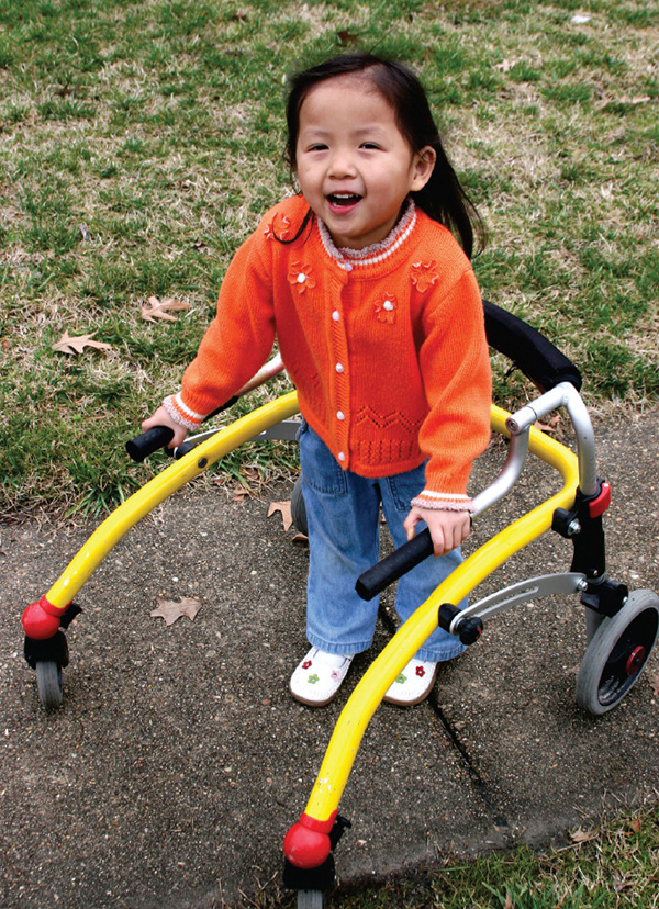 Young girl with cerebral palsy using a walker to move independently.