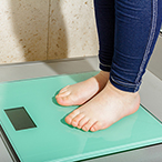 A child's feet and ankles on a bathroom scale.