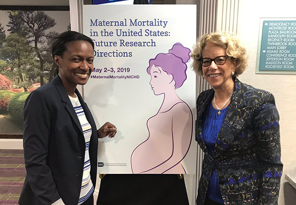 Cynthia Giamfi-Bannerman, M.D., of Columbia University, and Diana Bianchi, M.D., NICHD Director, standing near a poster for NICHD's Maternal Mortality workshop.