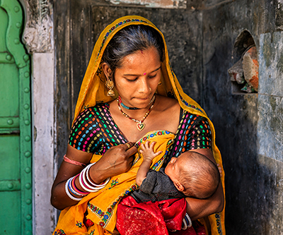 A young Indian mother breastfeeding her newborn baby.
