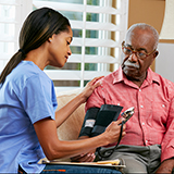 A nurse takes the blood pressure of an elderly man. Both are African-American.