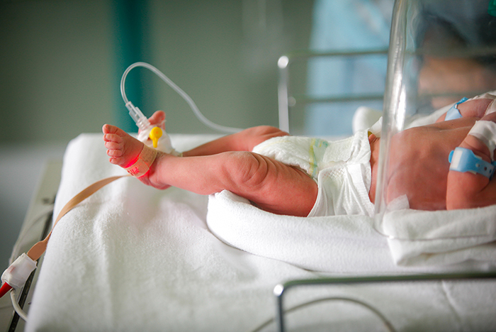 An infant in an incubator, with an oxygen sensor on one foot and an intravenous line on the other foot.