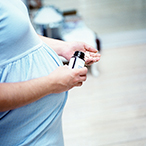 Pregnant woman taking pills out of a bottle.