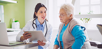 An older, white-haired woman looks at a chart with her doctor, a younger woman.
