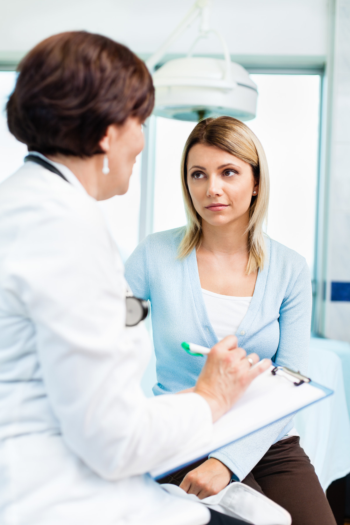 Medical professional with pen and clipboard talking with woman who looks concerned.