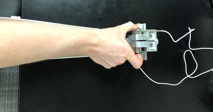 A hand holding the device used to measure grip strength.