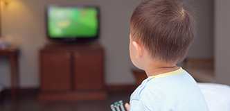 A child holding a television remote control device, facing a television set.
