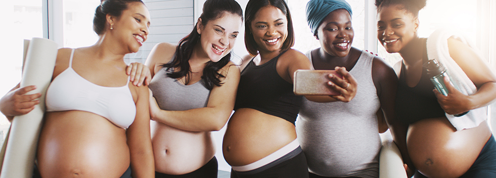 Five smiling pregnant women of various body types, four with their abdomens exposed, taking a selfie. Pregnancy for Every Body.
