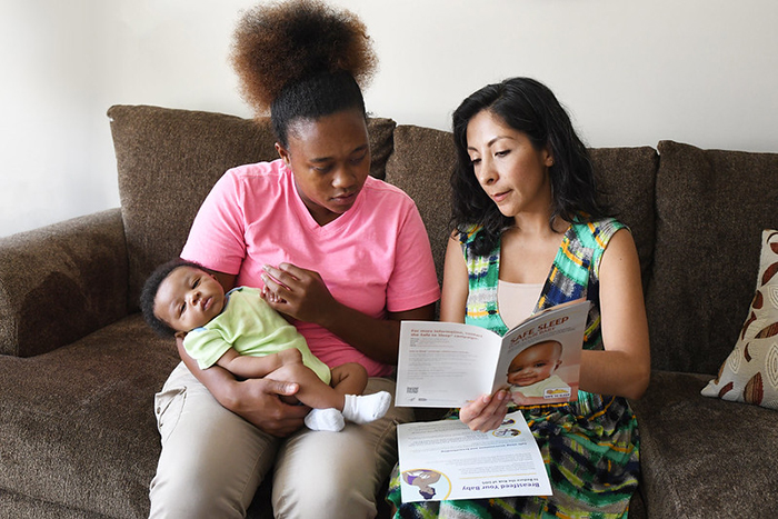 New mom with infant looks over Safe Infant Sleep recommendations with another woman.