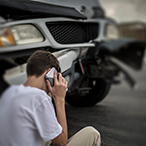 Teenage boy, sitting on curb, talking on a cell phone, in front of a car with front end collision damage.