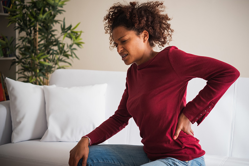 Adolescent woman rubbing back with one hand while grimacing in pain.