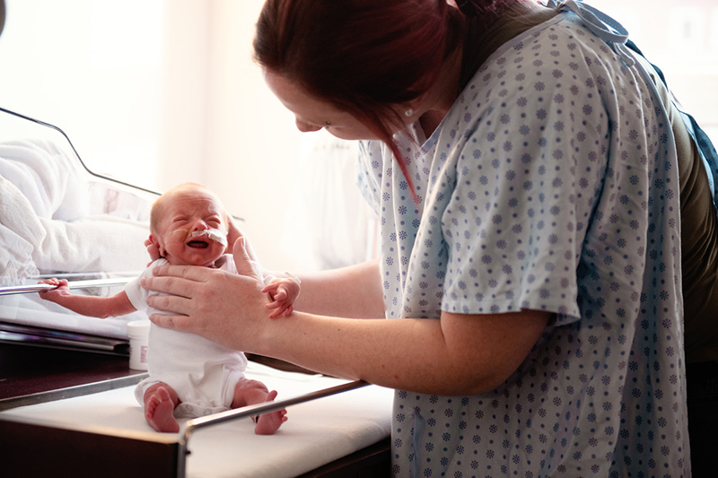 Woman in hospital gown supports preterm infant seated on table.