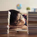 Teen male resting his head on a desk between two stacks of books.
