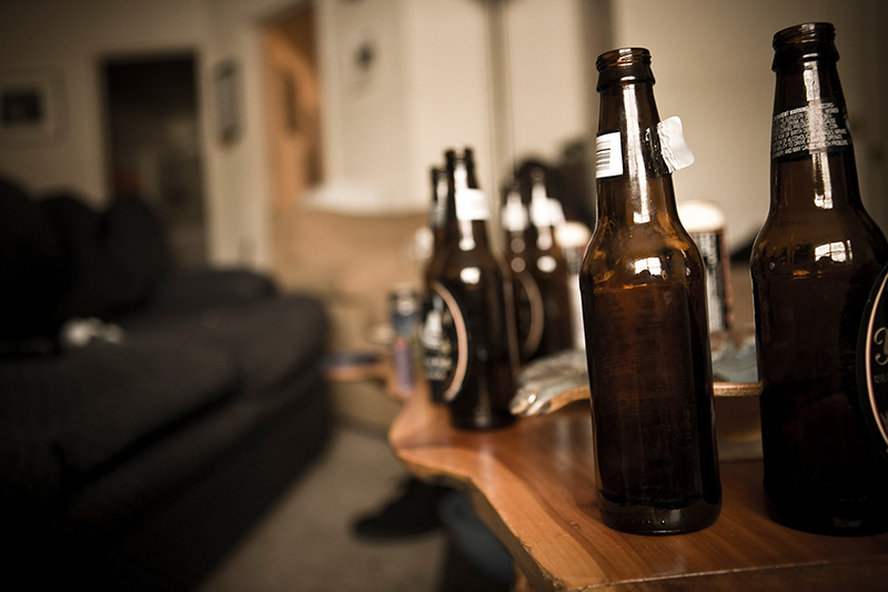 Multiple empty beer bottles on a coffee table.