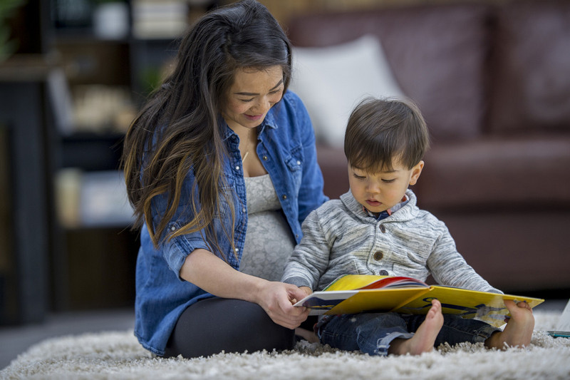 Woman and child sitting on a rug reading a book together.