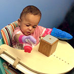 A toddler in a high chair, playing with toys.