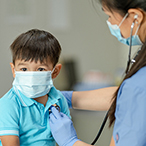 Boy seated while healthcare provider listens to his heart with a stethoscope.