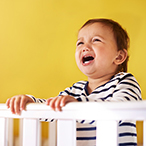 Infant standing behind crib rail, crying.