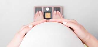 Point-of-view image of pregnant woman looking over abdomen at feet on scale.
