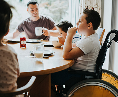 A boy sitting in a wheelchair at a table, eating a meal with his family.