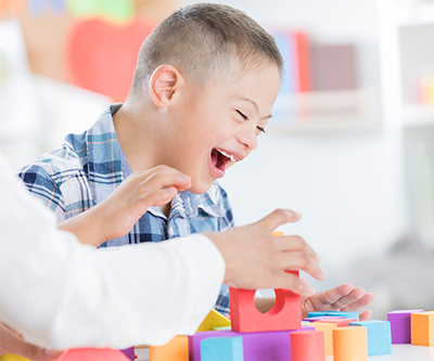 A young boy with Down syndrome laughing as he plays with building blocks.