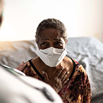 African American woman in healthcare provider's office wearing a mask and speaking to a provider.