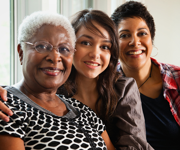 Image of 3 smiling women who are from different generations within a family.