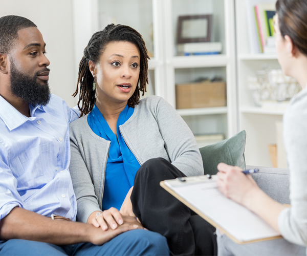 Image of an African American couple speaking to a healthcare provider, who is holding a clipboard.