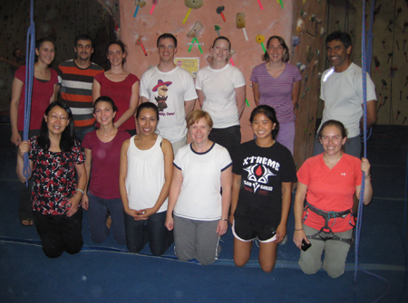 Lab members pose for a photo in a rock climbing gym.